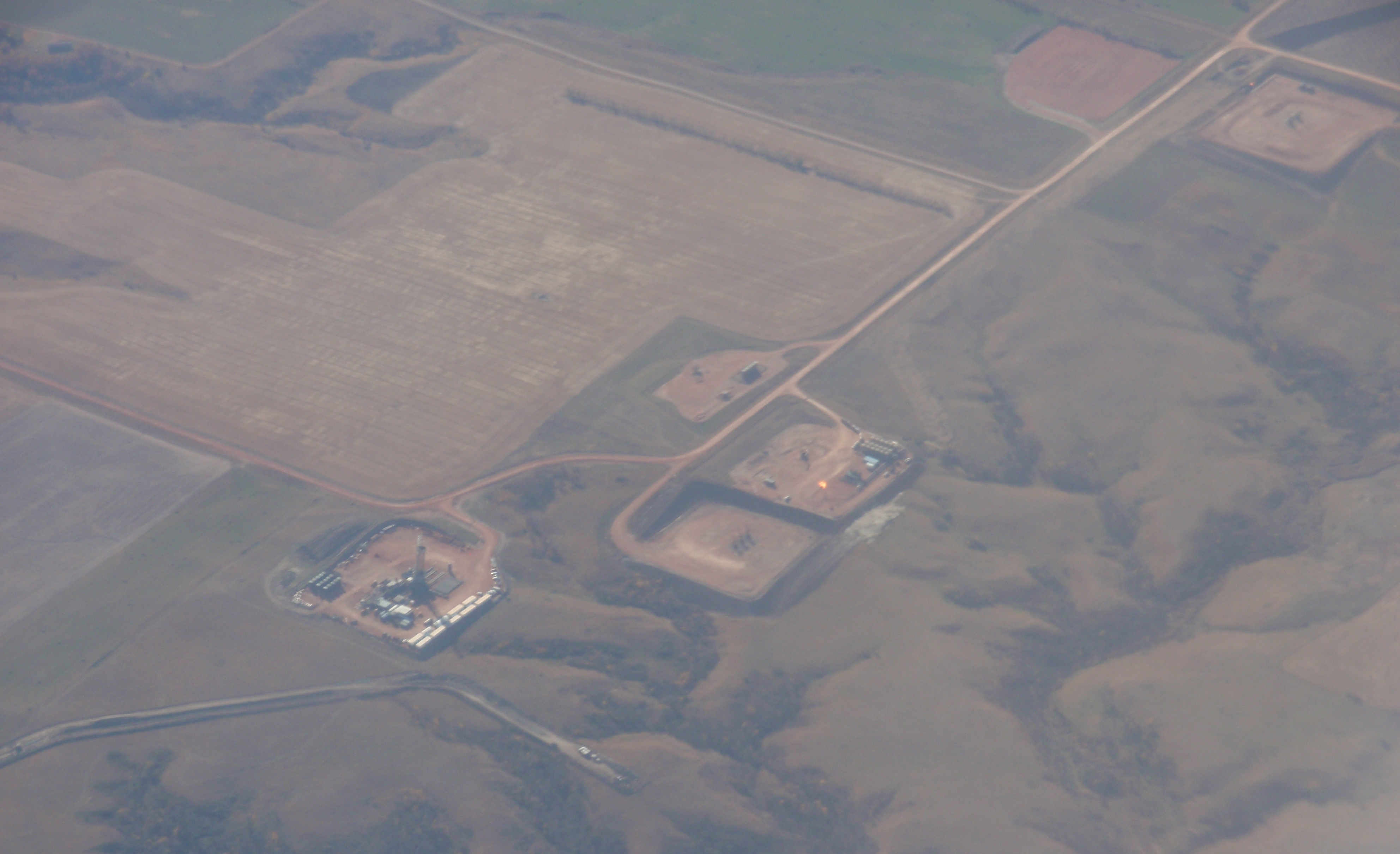5 oil pads in North Dakota, 1 with drilling rig and one cleared ready to drill. Photo by James Ulvog