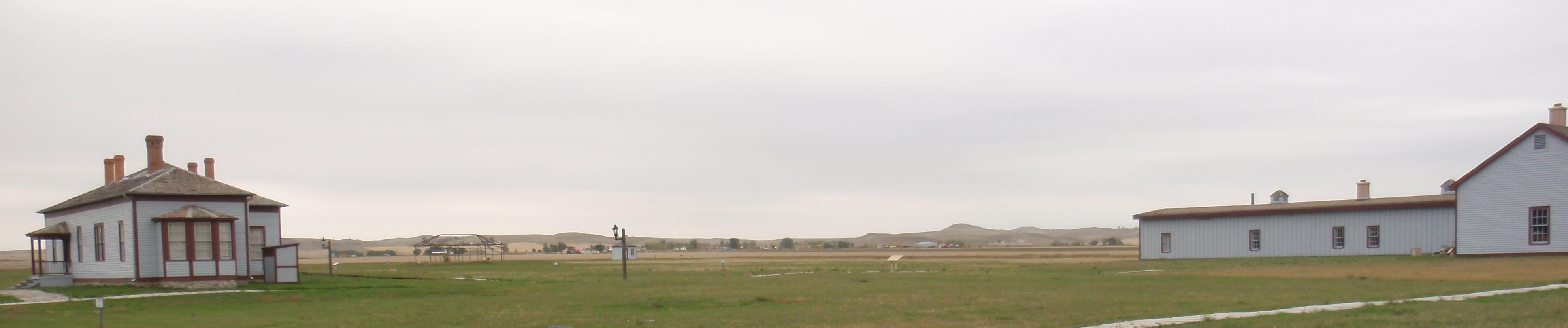 Reconstructed commander's quarters and barracks. There are about 5 well sites in the panorama. Consider that as an indicator of the low density and visibility of oil wells. Photo by James Ulvog.