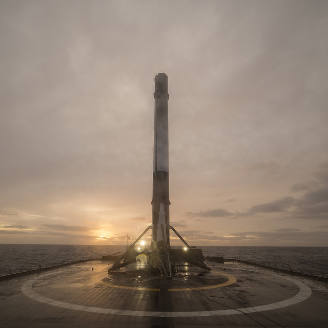 Falcon 9 booster recovered. Credit Flickr. Courtesy of SpaceX who has placed their photos in the public domain.