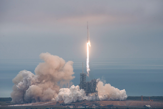 Liftoff of Falcon 9 and Dragon capsule on CRS-10 mission. Credit Flickr. Courtesy of SpaceX who has placed their photos in the public domain.